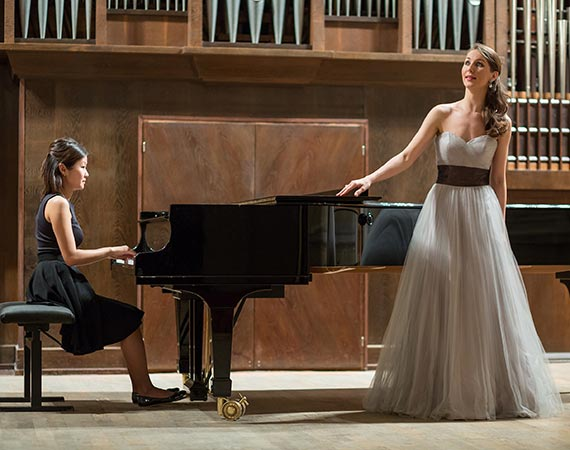 A woman stands before a piano and sings while another woman plays